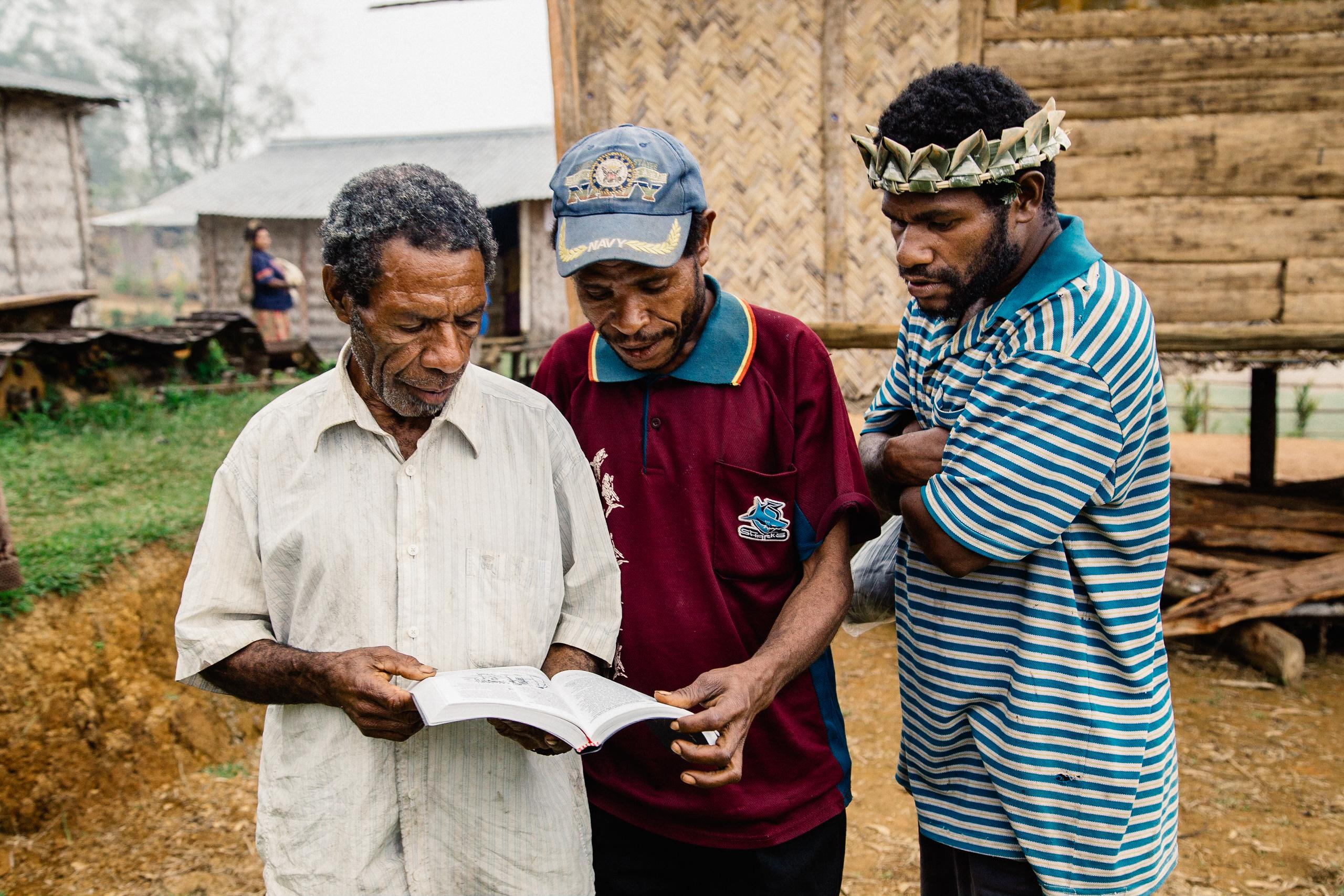 Three Men in Papua New Guinea Reading Scripture